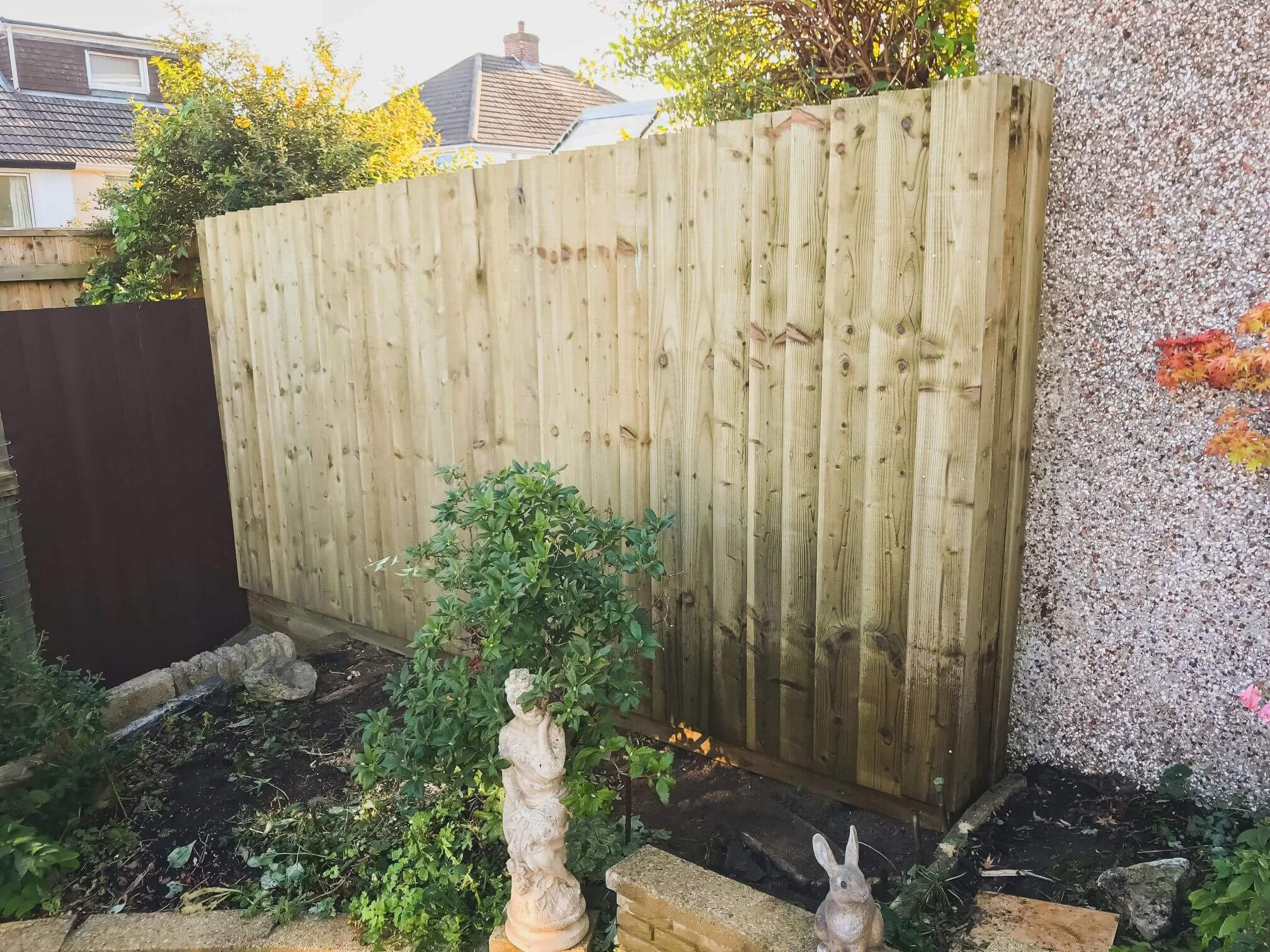 Fencing Solutions Plymouth - Image of a section of wooden feather edge fencing, surrounded by plants and garden statues