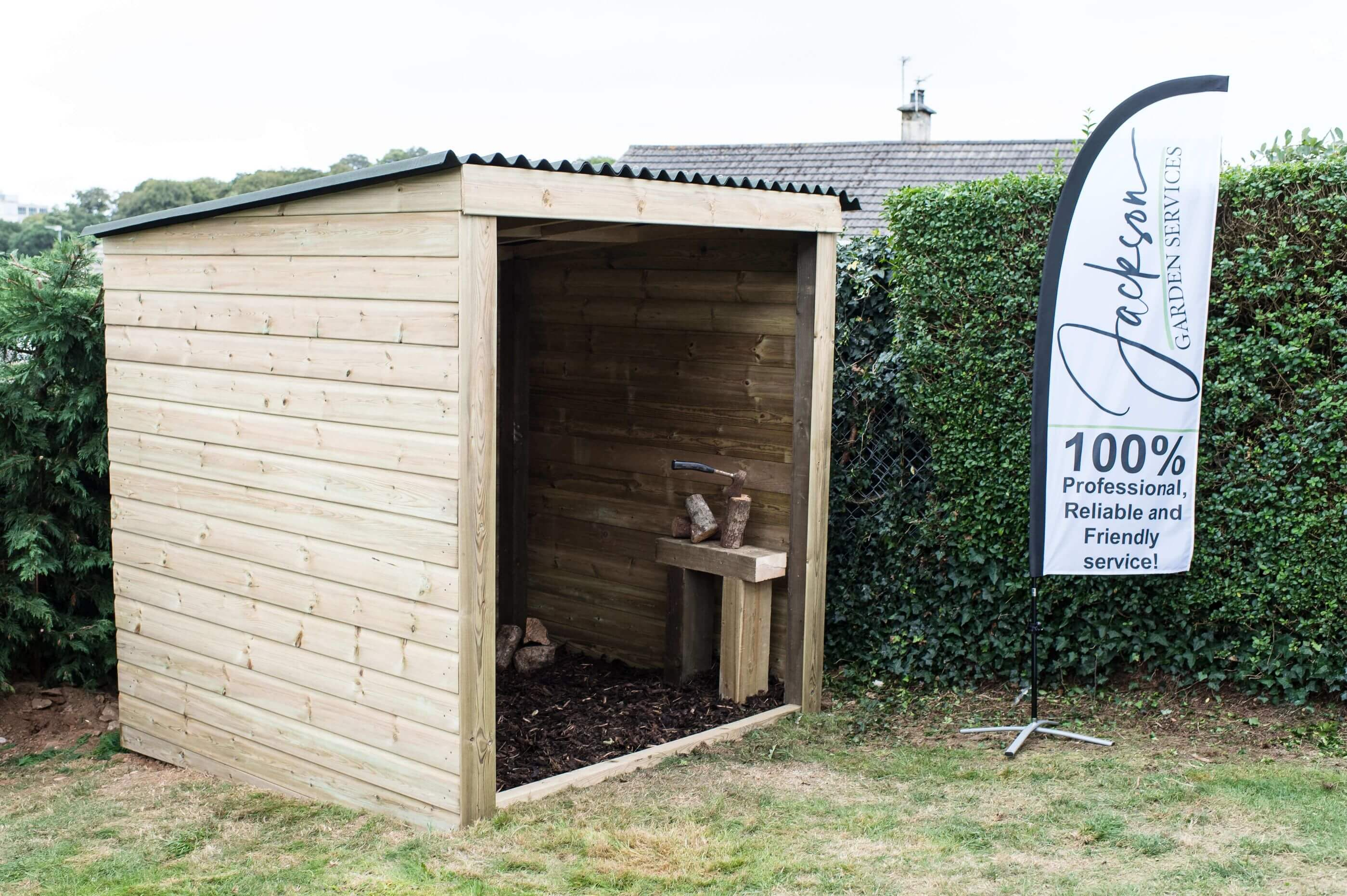 Sheds & Outbuildings - Image of a wooden log store garden shelter next to a Jackson Garden Services flag