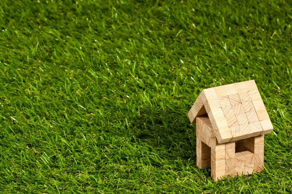 Artificial Grass Benefits: Close up image of an artificial lawn with a small toy wooden house in the bottom right hand corner.