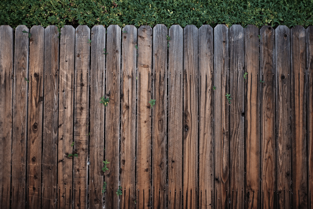 Fence Inspection: Image of an old dark brown picket fence.