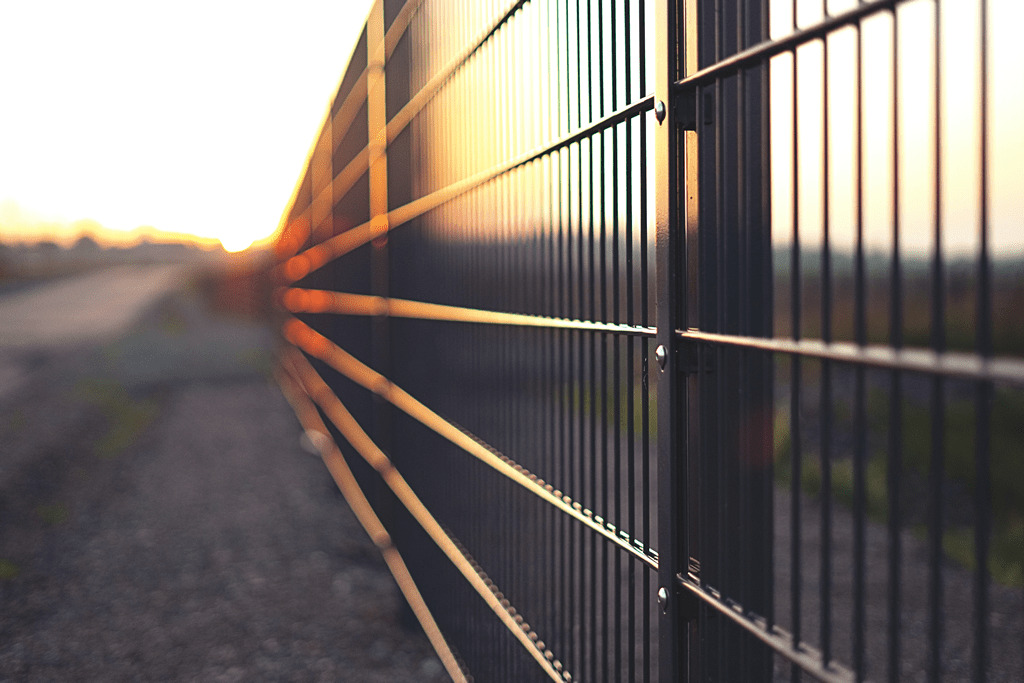 Fencing Repair - Image of metal commercial fencing at sunset.