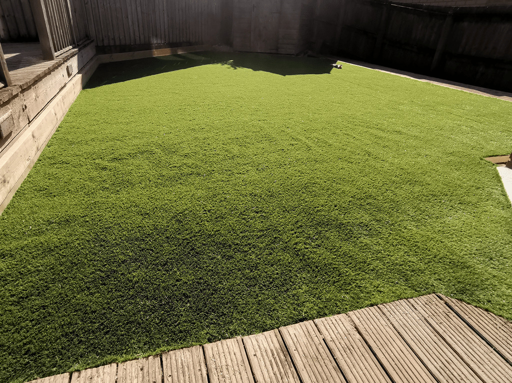 Turf Services: Image of a newly laid lawn, surrounded by decking.